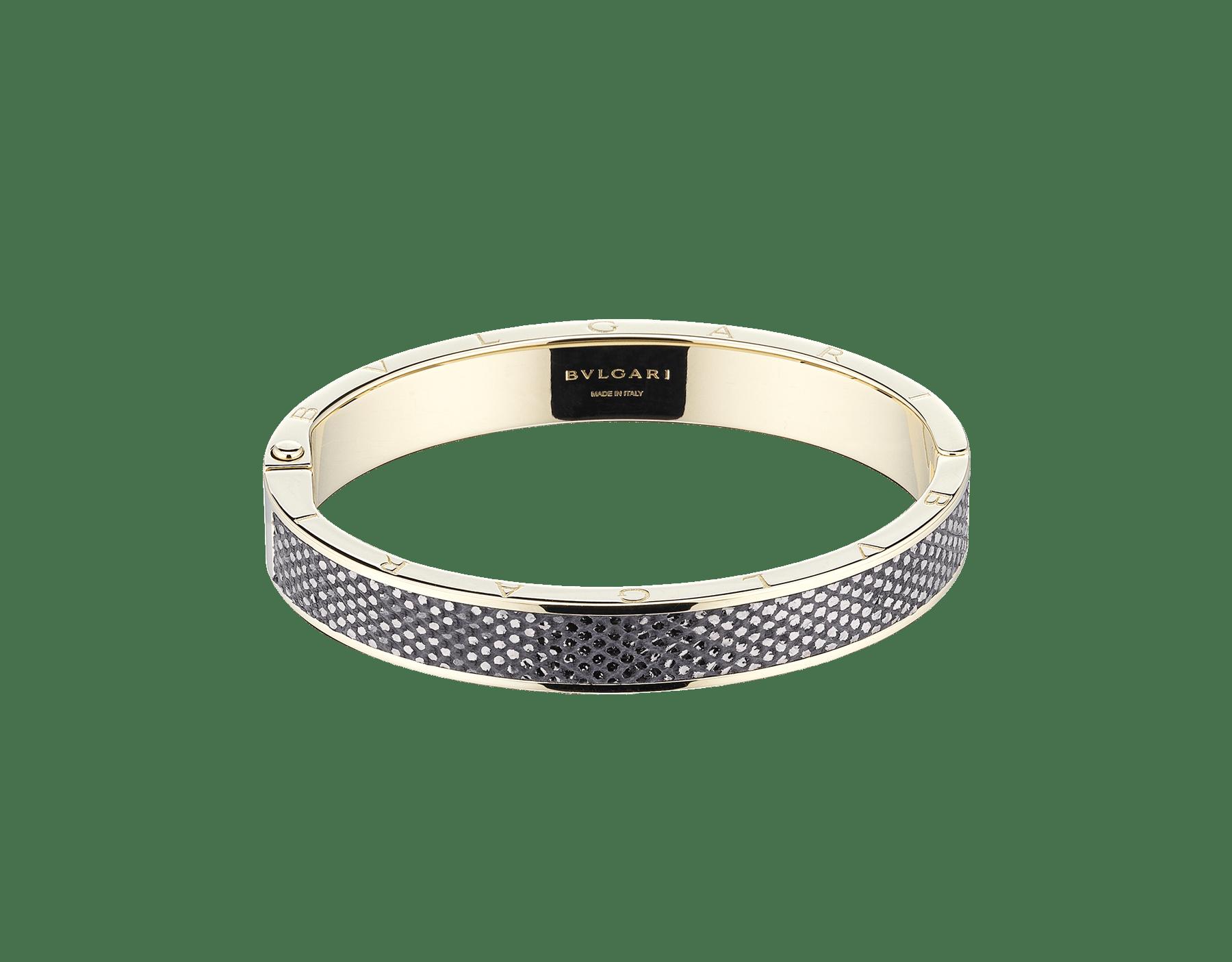 """BVLGARI BVLGARI"" bangle bracelet in light gold-plated brass with a Charcoal Diamond grey metallic karung skin insert and a BVLGARI logo hinge closure. Logo engraving along the edges of both sides of the bracelet and in the inner part. HINGELOGOBRACLT-MK-CD image 2"