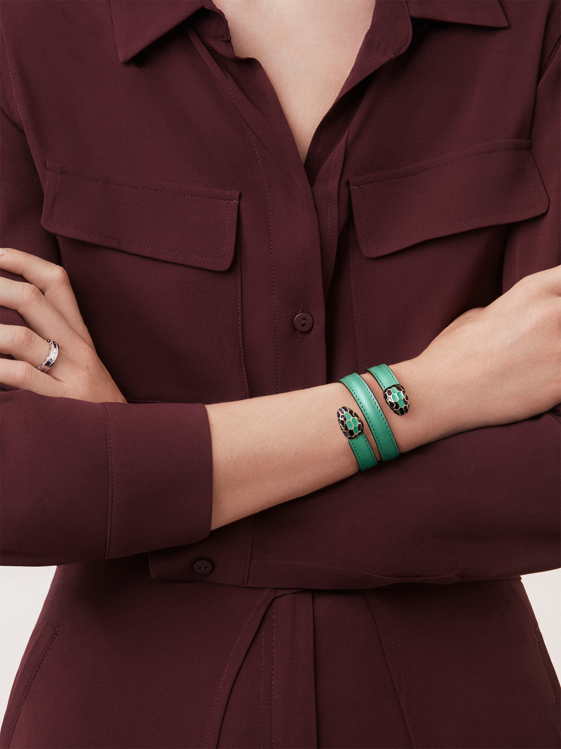 Multi-coiled rigid bracelet in emerald green calf leather with brass light gold plated hardware. Double tempting Serpenti head finished in black and tone on tone enamel. Cleopatra-CL-EG image 2