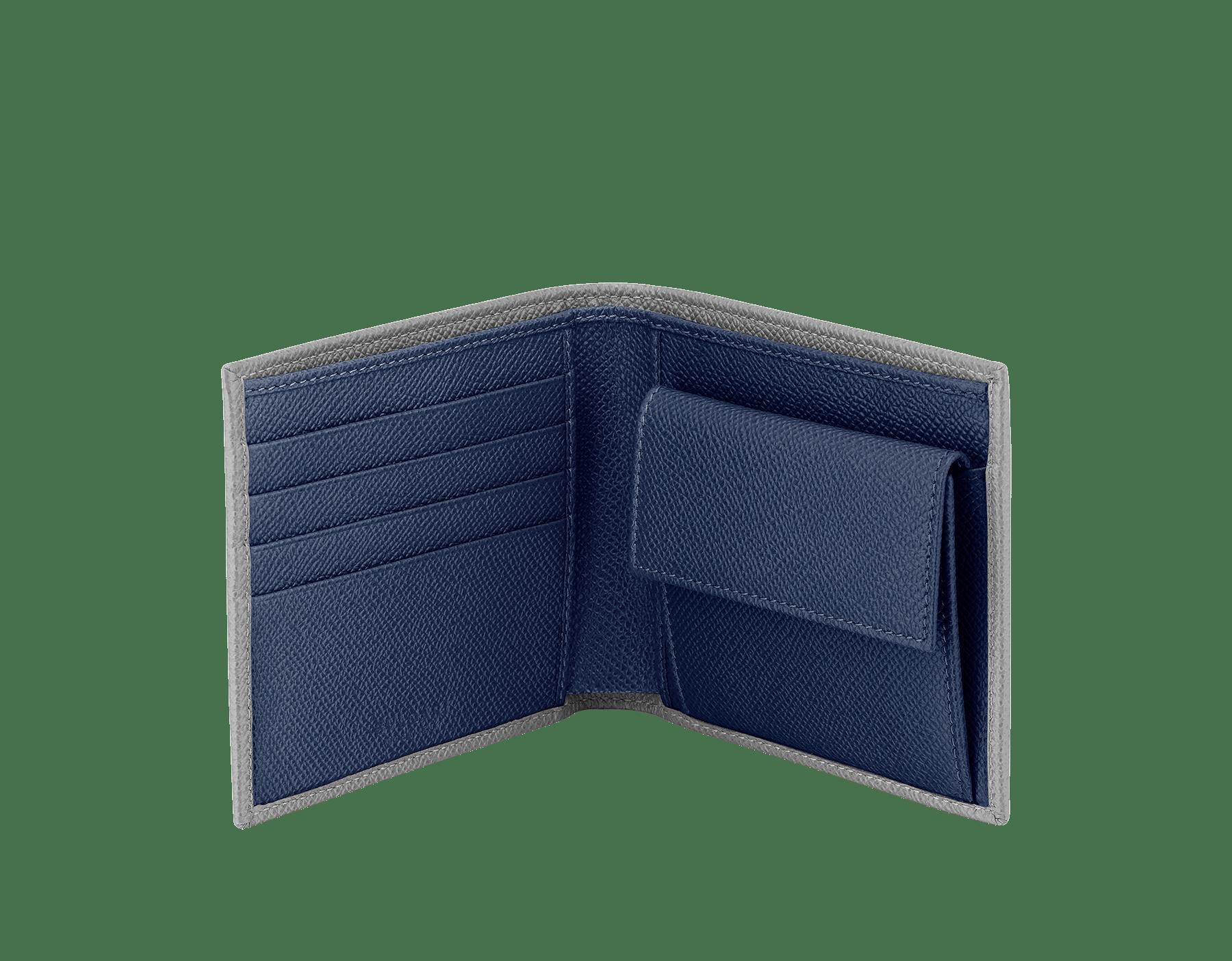 プルートストーングレーとデニムサファイアブルーのグレインカーフレザーを使った「ブルガリ・ブルガリ」メンズコンパクトウォレット。 パラジウムプレートブラス製のアイコニックなロゴの装飾。 BBM-WLT-ITAL-gcl image 2
