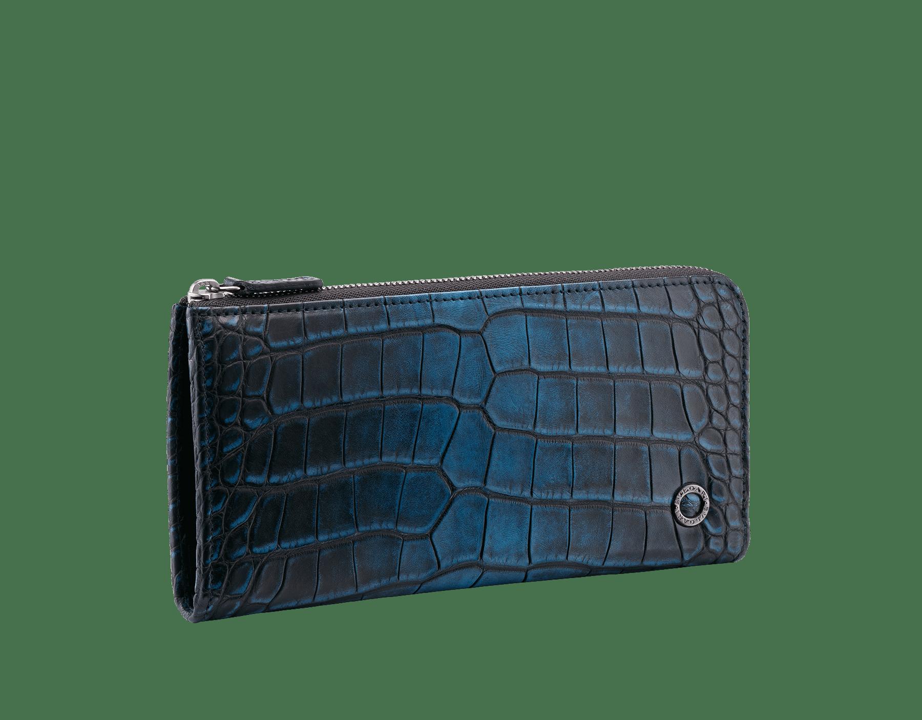 Portefeuille à fermeture éclair en L en alligator bleu nuit et cuir de veau lisse noir avec détails en laiton plaqué ruthénium foncé ornés du motif BVLGARI BVLGARI. 38932 image 1