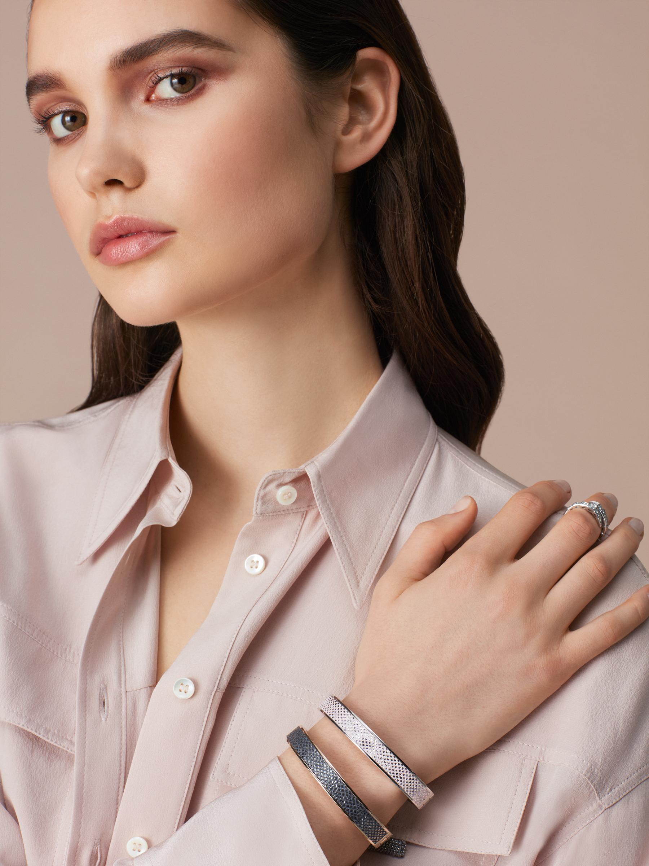 """BVLGARI BVLGARI"" bangle bracelet in palladium-plated brass with a Rosa di Francia pink metallic karung skin insert and a BVLGARI logo hinge closure. Logo engraving along the edges of both sides of the bracelet and in the inner part. HINGELOGOBRACLT-MK-RdF image 3"
