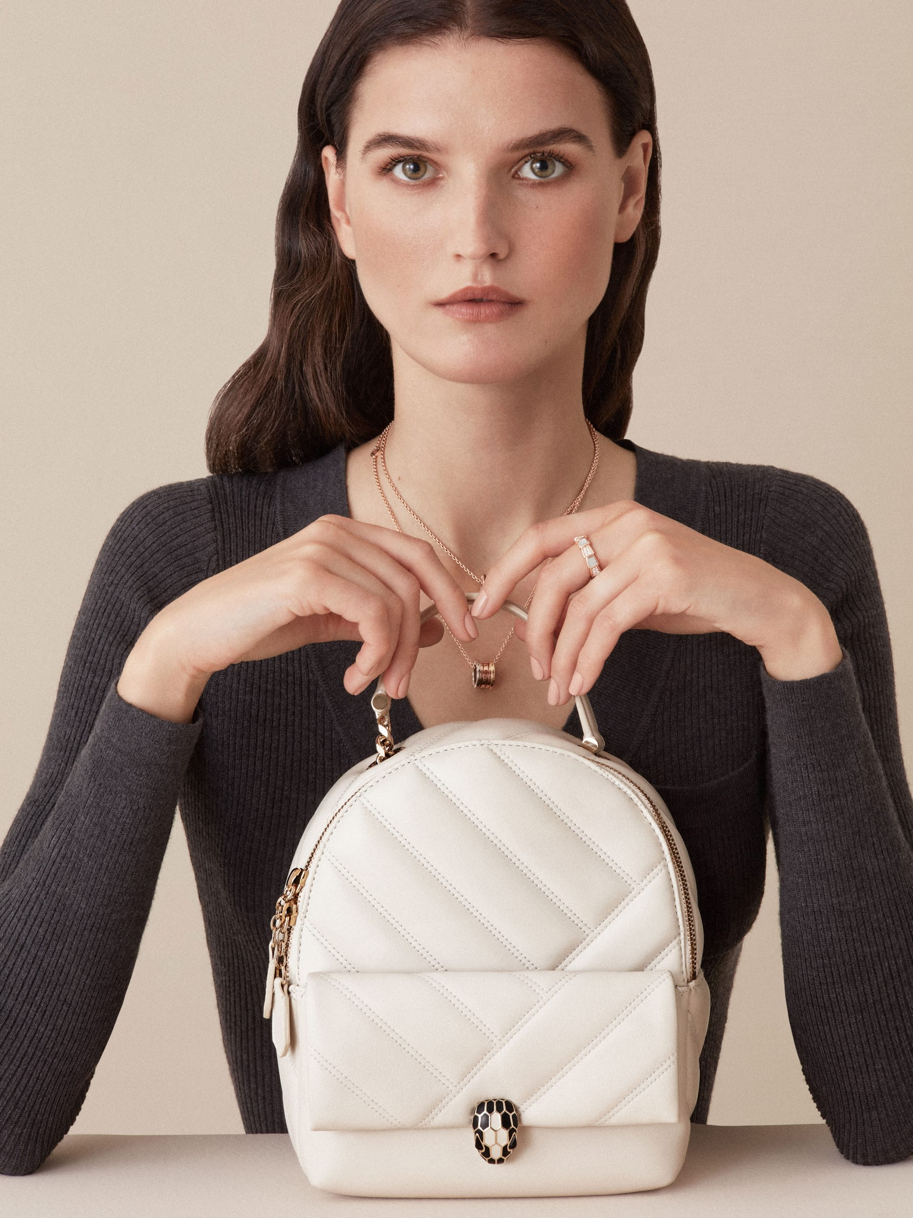 Serpenti Cabochon backpack in soft quilted white agate calf leather, with a graphic motif. Light gold plated brass tempting snake head closure in black and white agate enamel and black onyx eyes. 1009-NSM image 6