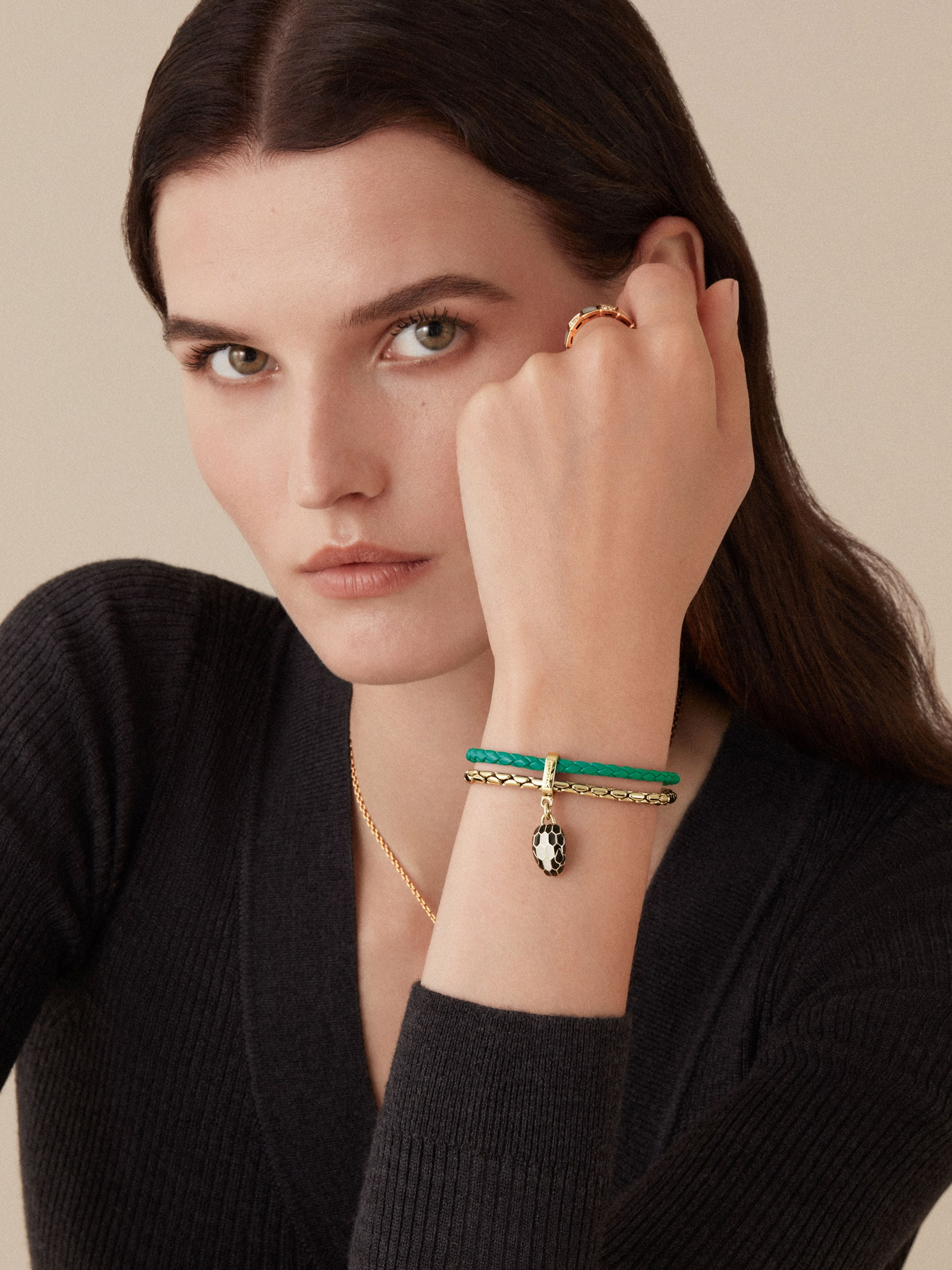 """""""Serpenti Forever"""" bracelet in braided, emerald-green calfskin with snake body-shaped chain in light gold-plated brass, iconic snakehead charm in black and agate-white enamel, black enamel eyes and magnetic clasp fastening. SerpBraidChain-WCL-EG image 3"""